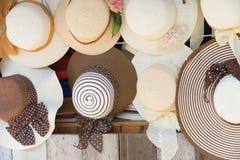 Sombreros de paja para la venta, colgando en una pared Imagen de archivo