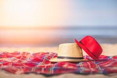 Sombreros de paja rojos y blancos en la playa Imágenes de archivo libres de regalías