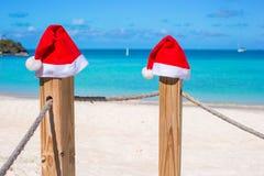 Sombreros de Papá Noel del primer dos en la cerca en el blanco tropical Foto de archivo libre de regalías