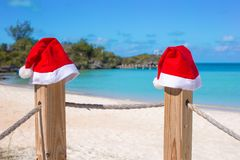 Sombreros de Papá Noel del primer dos en la cerca en el blanco tropical Fotos de archivo libres de regalías