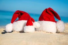 Sombreros de Papá Noel en la playa arenosa - concepto de Año Nuevo Imágenes de archivo libres de regalías
