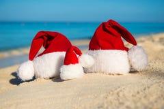 Sombreros de Papá Noel en la playa arenosa - concepto de Año Nuevo Fotografía de archivo