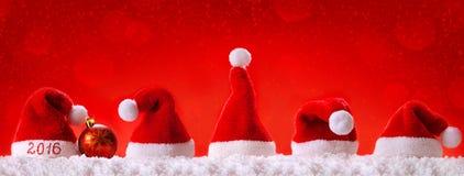 Sombreros 2016 de santa de la Feliz Año Nuevo Siete sombreros rojos de santa Imagen de archivo libre de regalías