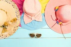 Sombreros hermosos del verano con las gafas de sol en fondo de madera azul Fotos de archivo