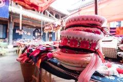 Sombreros para los trajes tradicionales de Yunnan en la exhibición en un mercado Imagenes de archivo