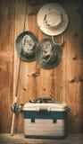 Sombreros que cuelgan en la pared con el equipo de pesca Fotos de archivo libres de regalías