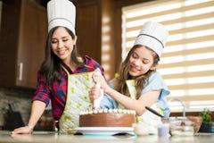 Sombreros y adornamiento del cocinero que llevan de una torta Imagen de archivo libre de regalías