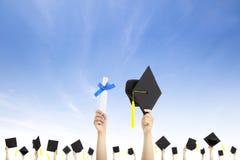 Sombreros y diploma de la graduación de la explotación agrícola de la mano imágenes de archivo libres de regalías