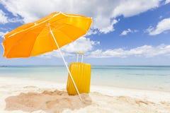 Sombrilla anaranjada con la carretilla amarilla Imagen de archivo