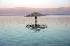 Sombrilla sola en el medio del mar muerto Fotos de archivo