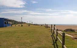Sombrillas y barrera de madera en área recreativa de la hierba foto de archivo