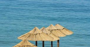 Sombrillas y mar de la paja de la playa imagen de archivo