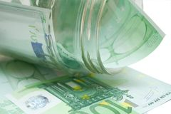 Some 100 euros. Banknotes in jar over white isolated background stock image