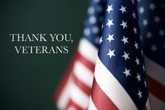 Text thank you veterans and american flags. Some american flags and the text thank you veterans against a dark green background Royalty Free Stock Photography