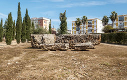 Some ancient stones. Is located in the remains of the ancient Roman civilization in Merida Augusta Emerita, Spain. It´s surrounded by trees and the houses in Royalty Free Stock Image