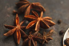 Anise stars on dark background. Some anise stars and black peper out of focus on old dark background. Selective focus Royalty Free Stock Image