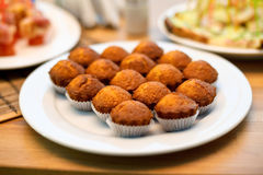 Some appetizing plain muffins in a white ceramic plate on a set table. Closeup of some appetizing plain muffins in a white ceramic plate on a set table Royalty Free Stock Image
