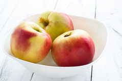 Some apples in the plate. Red and yellow apples in the plate on white wooden table. Selective focus Stock Image