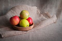 Some apples in wooden plate on a linen tablecloth with burlap and ears of wheat. Lit by the sun light stock photos