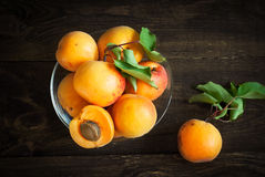 Some apricots in a bawl. Some ripe apricots in a glass bowl on a wooden table Selective fokus Stock Images