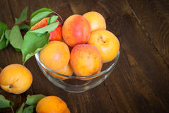 Some apricots in a bawl. Some ripe apricots in a glass bowl on a wooden table Selective fokus Stock Photo