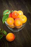Some apricots in a bawl. Some ripe apricots in a glass bowl on a wooden table Selective fokus Stock Photos