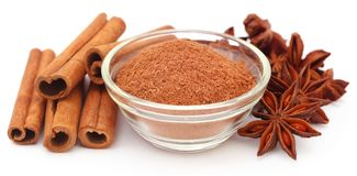 Some aromatic cinnamon with star anise and ground spice. In a bowl royalty free stock photography