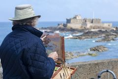 Some artist draws a painting in Saint-Malo, France. Some artist draws a painting with fortress in Saint-Malo, France Stock Photography