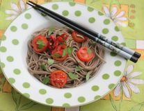 Asian noodles with tomatoes. Some asian somen noodles with coriander and tomatoes royalty free stock image