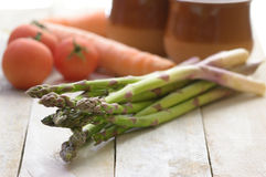 Some asparagus on a white wooden table in a rustic kitchen. Royalty Free Stock Photography