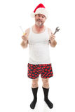 Some Assembly Required. Frustrated dad in a Santa hat holding his tools. He looks scruffy, like he's been up all night assembling Christmas presents. Full body royalty free stock image