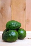 Some avocado fruits. On wooden shelf stock photography