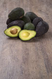Some avocados over a wooden surface. Fresh fruits Royalty Free Stock Photo