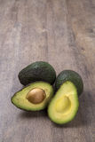 Some avocados over a wooden surface. Fresh fruits Royalty Free Stock Image