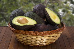 Some avocados over a wooden surface. Fresh fruits Royalty Free Stock Photos