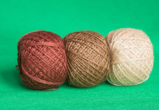 Some balls of a multi-colored yarn on a green background. Close up royalty free stock photo