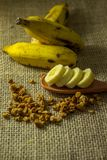 Some bananas and a banana sliced into a wooden spoon with cereal. And honey royalty free stock photography