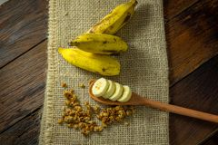 Some bananas and a banana sliced into a wooden spoon with cereal. And honey royalty free stock images