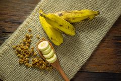 Some bananas and a banana sliced into a wooden spoon with cereal. And honey stock photography