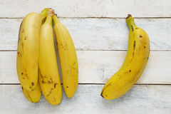 Some bananas on a white wooden table. A banana on a white wooden table. Top view Stock Images