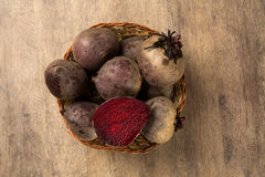 Some beets in a basket over a wooden surface. Some beets in a basket over a white background. Fresh vegetable Royalty Free Stock Photo