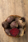 Some beets in a basket over a wooden surface. Some beets in a basket over a white background. Fresh vegetable Royalty Free Stock Images