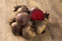 Some beets in a basket over a wooden surface Stock Photos