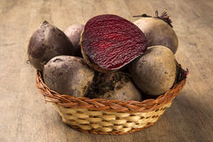 Some beets in a basket over a wooden surface. Some beets in a basket over a white background. Fresh vegetable Stock Image