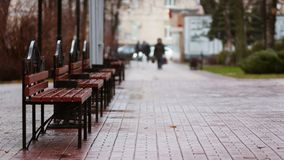 Some benches in the autumn park. Some benches stand in the autumn park. Blurred people go home or to work royalty free stock photos