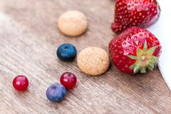 Some berries and Amarettini biscuits with napkin on wooden board. Landscape royalty free stock photography