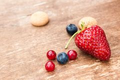 Some berries and Amarettini biscuits on wooden board Royalty Free Stock Images