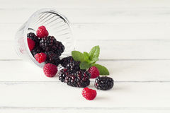 Some berries. Bowl with blackberries, raspberries and peppermint on white wooden Royalty Free Stock Photography