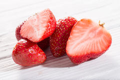 Some berries of strawberry, whole and cut, on white boards. Close up, horizontal shot Royalty Free Stock Photos