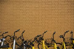 Some bikes parking outside a brick wall. Shot of some rental bikes parking just next to a large brown brick wall stock photo
